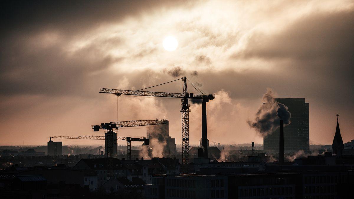 Baukräne und rauchende Schornsteine im Münchner Stadtteil Maxvorstadt bei Abendsonne.