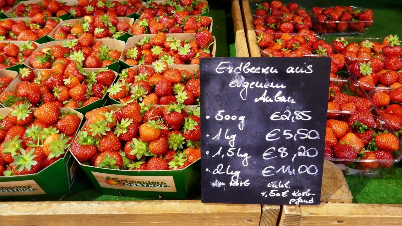 """Erdbeeren in Pappschalen an einem Verkaufsstand. Auf einer Tafel steht """"Erdbeeren aus eigenem Anbau""""."""