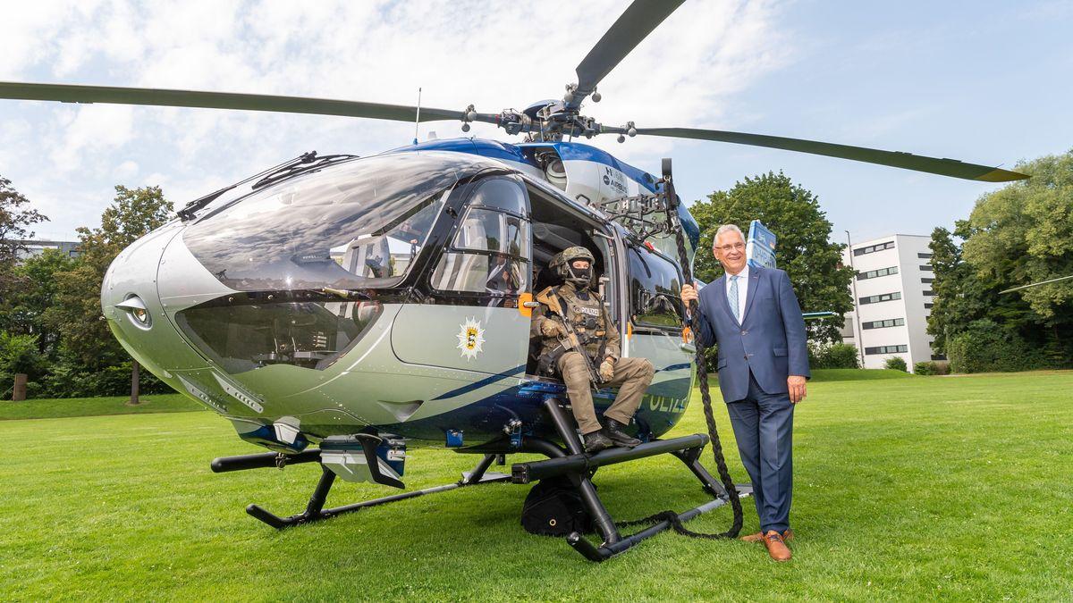 Joachim Herrmann, Innenminister von Bayern, steht vor einem Hubschrauber der Polizei Baden-Württemberg