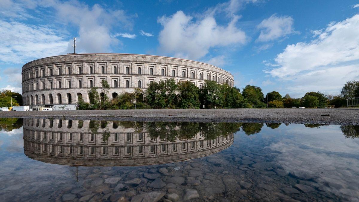 Die Kongresshalle im Nürnberger Reichsparteitagsgelände verdoppelt sich durch die Spiegelung in einer Pfütze.