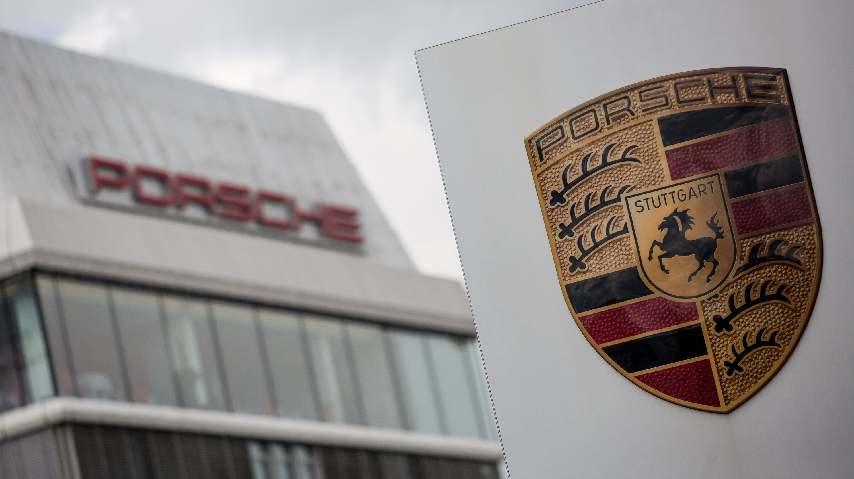 Das Porsche Logo ist vor einem Gebäude des Automobilherstellers zu sehen.