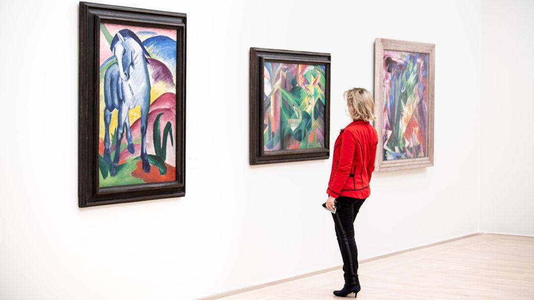 """Eine Frau steht in der Ausstellung """"Der Blaue Reiter - Gruppendynamik"""" im Lenbachhaus neben dem Gemälde """"Blaues Pferd I"""" von Franz Marc."""
