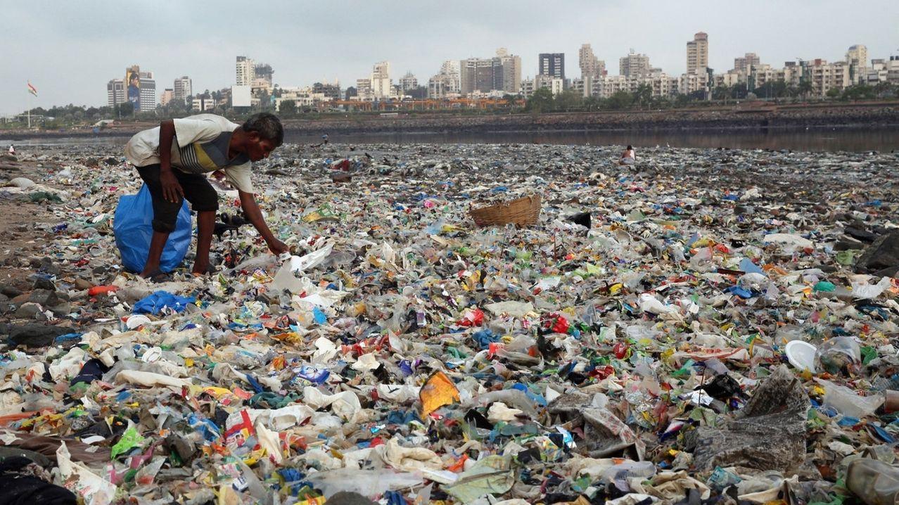 Plastikmüll am Meer:  Ein Mann sammelt im indischen Mumbai Plastik und andere wiederverwertbare Materialen an der von Plastiktüten und sonstigen Müll übersäten Küste des Arabisches Meeres.