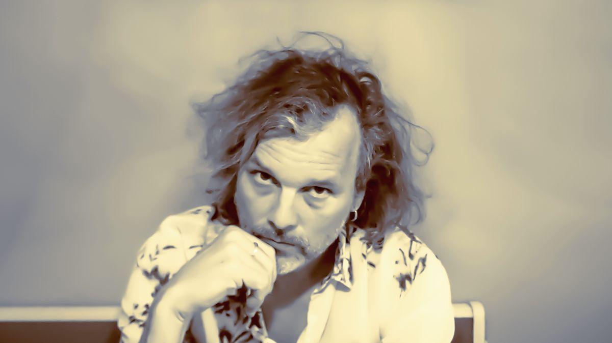 Ein Porträt des Musikers und Filmkomponisten Gerd Baumann mit wuscheligen Haaren und gemustetertem Hemd