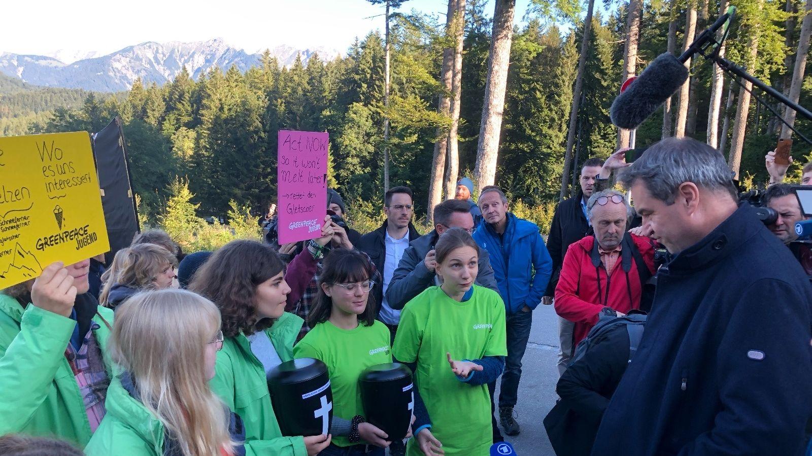 Ministerpräsident Söder (CSU, r.) im Gespräch mit Greenpeace-Vertreterinnen, die Urnen mit geschmolzenem Gletscherwasser in den Händen halten