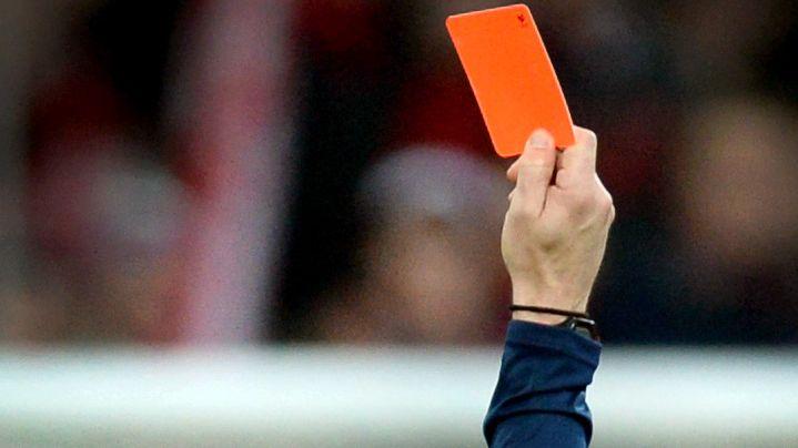Ein Schiedsrichter zeigt einem Fußballspieler die rote Karte.