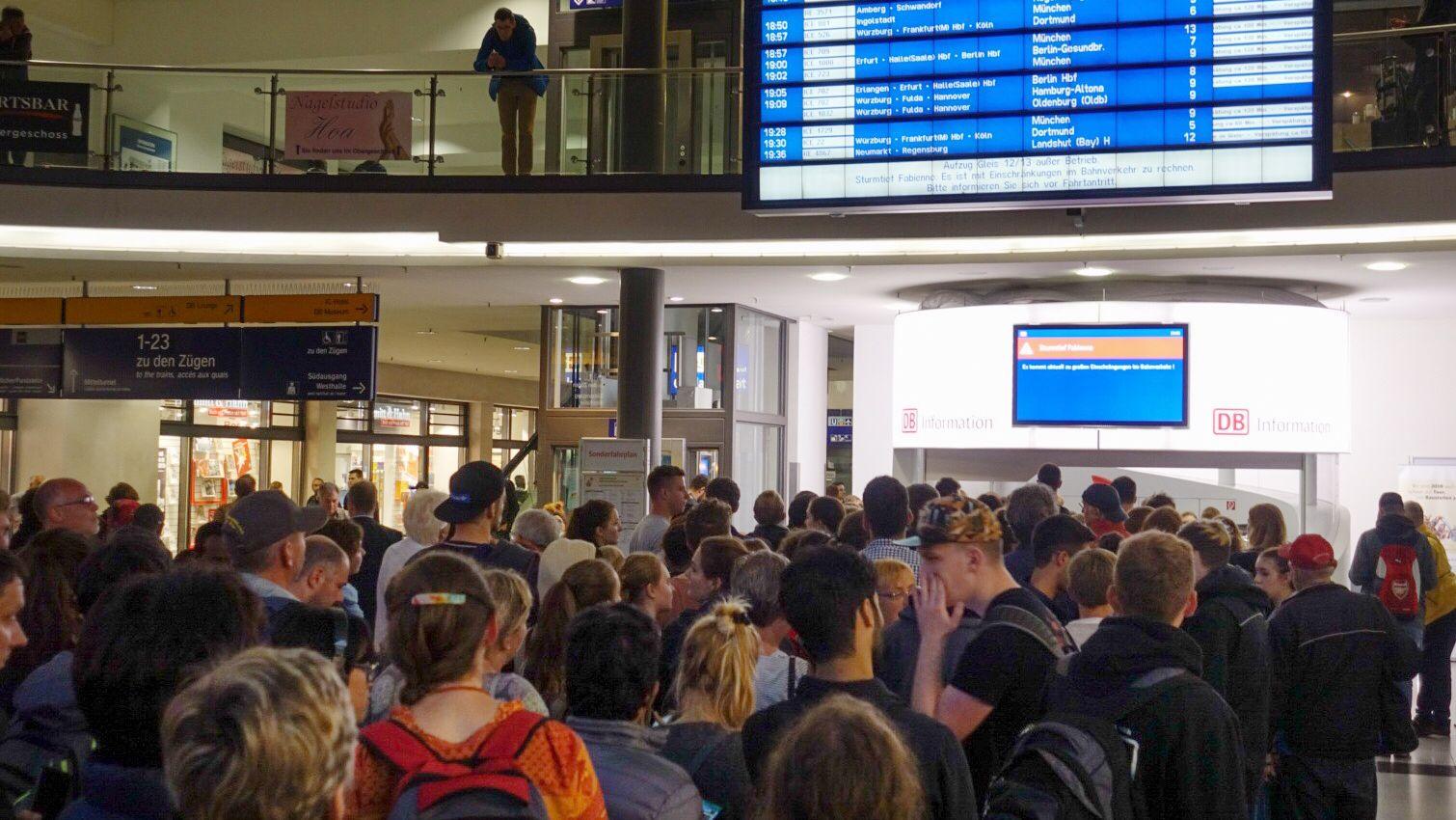 Reisende schauen auf einen Monitor im Hauptbahnhof von Nürnberg
