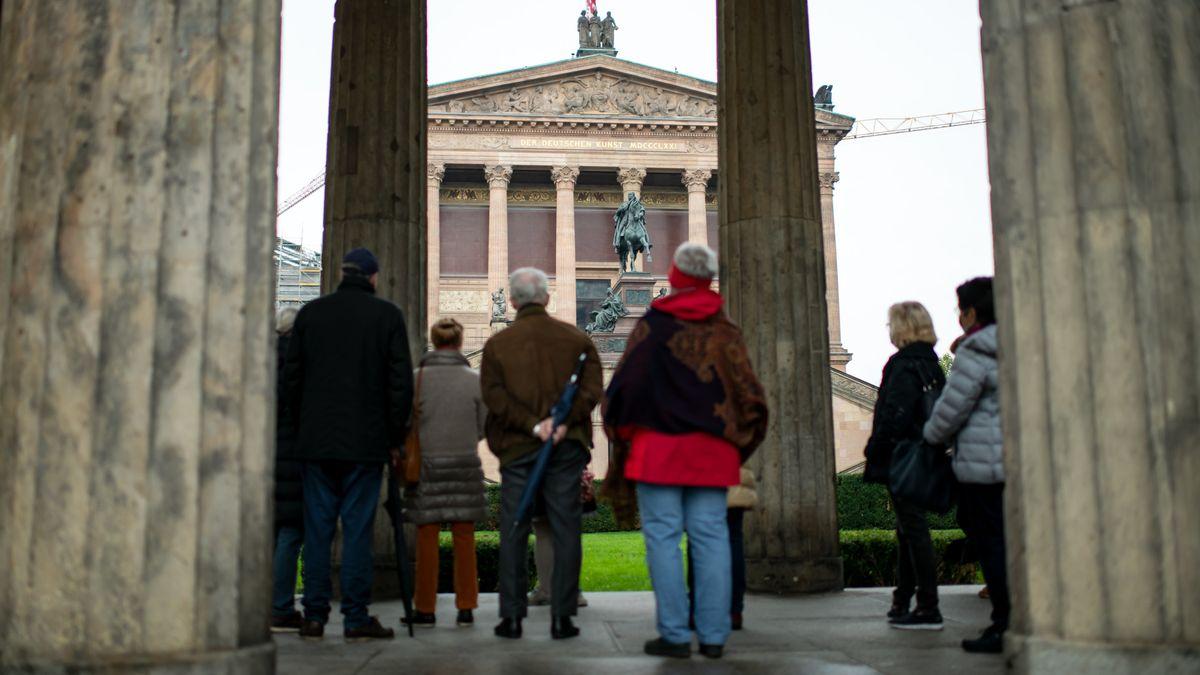 Touristen stehen auf der Museumsinsel zwischen Säulen vor der Alten Nationalgalerie.