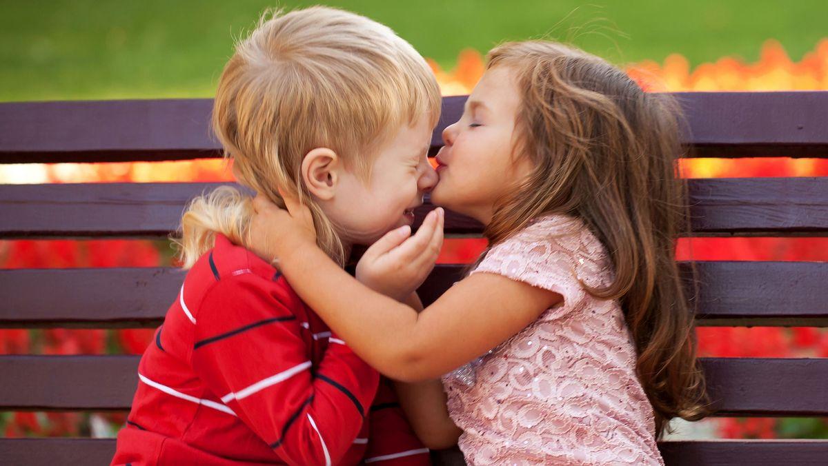 Zwei sich umarmende Kinder auf einer Bank