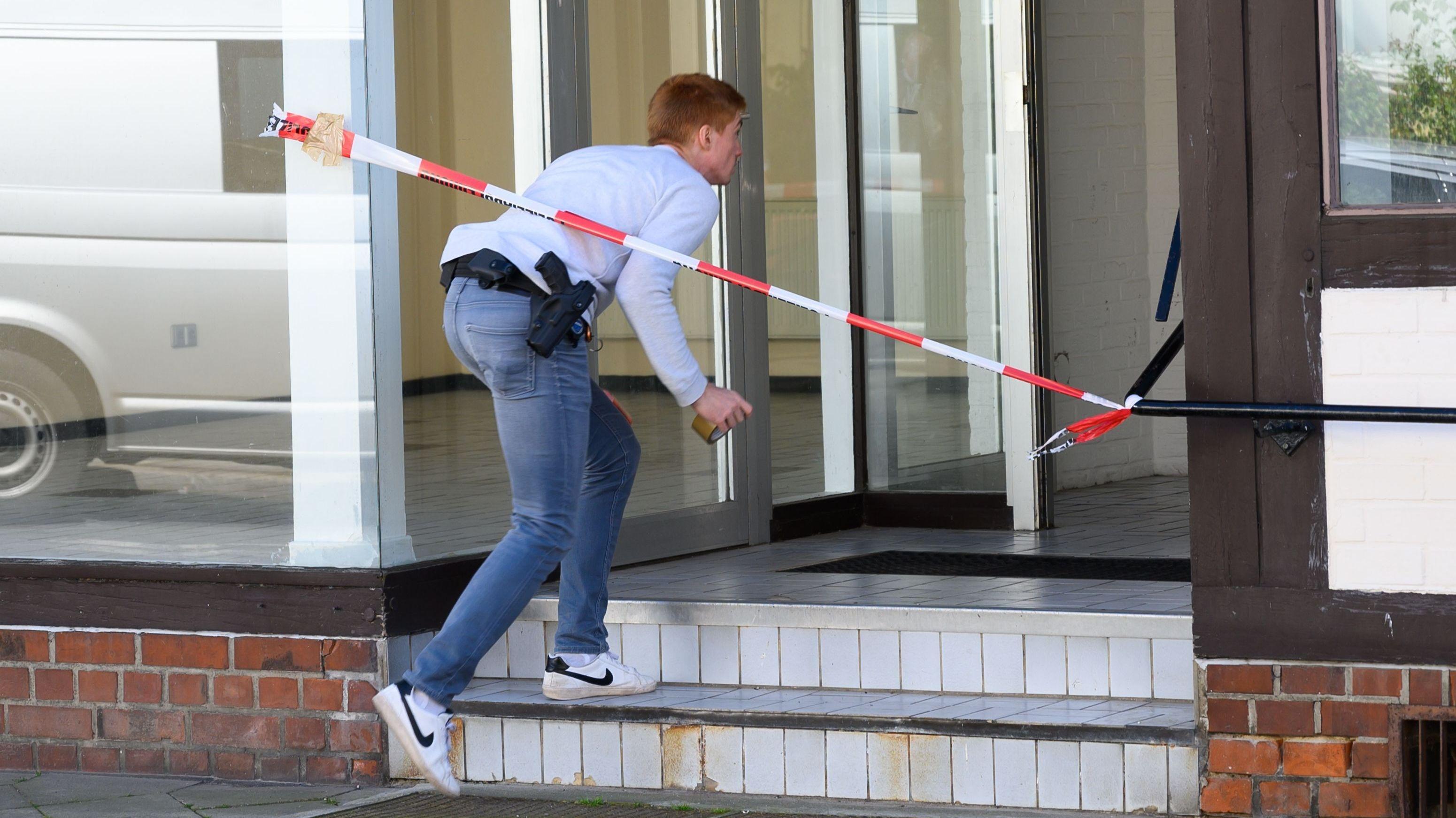 Ein Ermittler betritt das Haus, in dem die Leichen gefunden wurden