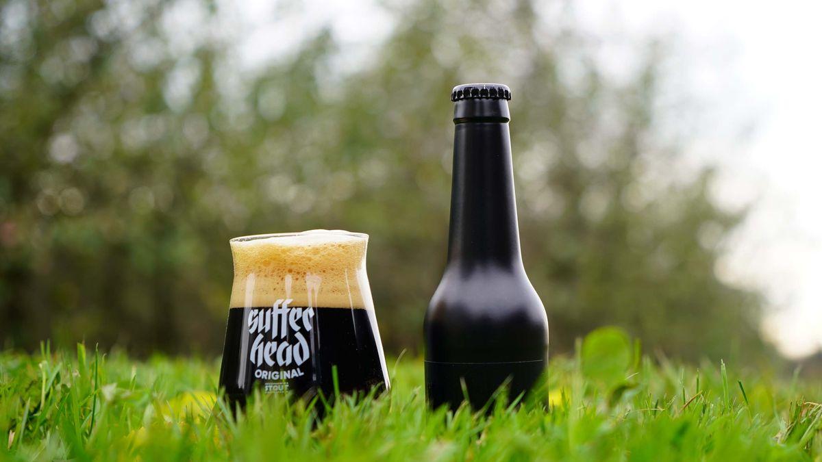 """Auf einer grünen Wiese steht ein Bierglas mit schwarzen Bier und der Aufschrift """"Sufferhead"""", daneben eine schwarze Bierflasche"""