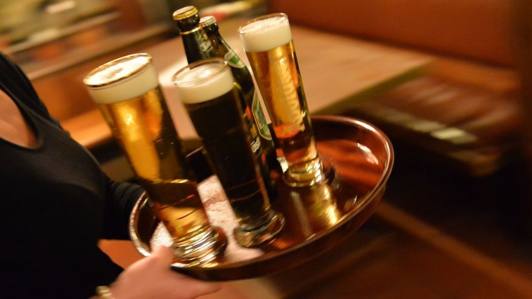 Eine Bedienung trägt in einem Lokal ein Tablett mit Bier.