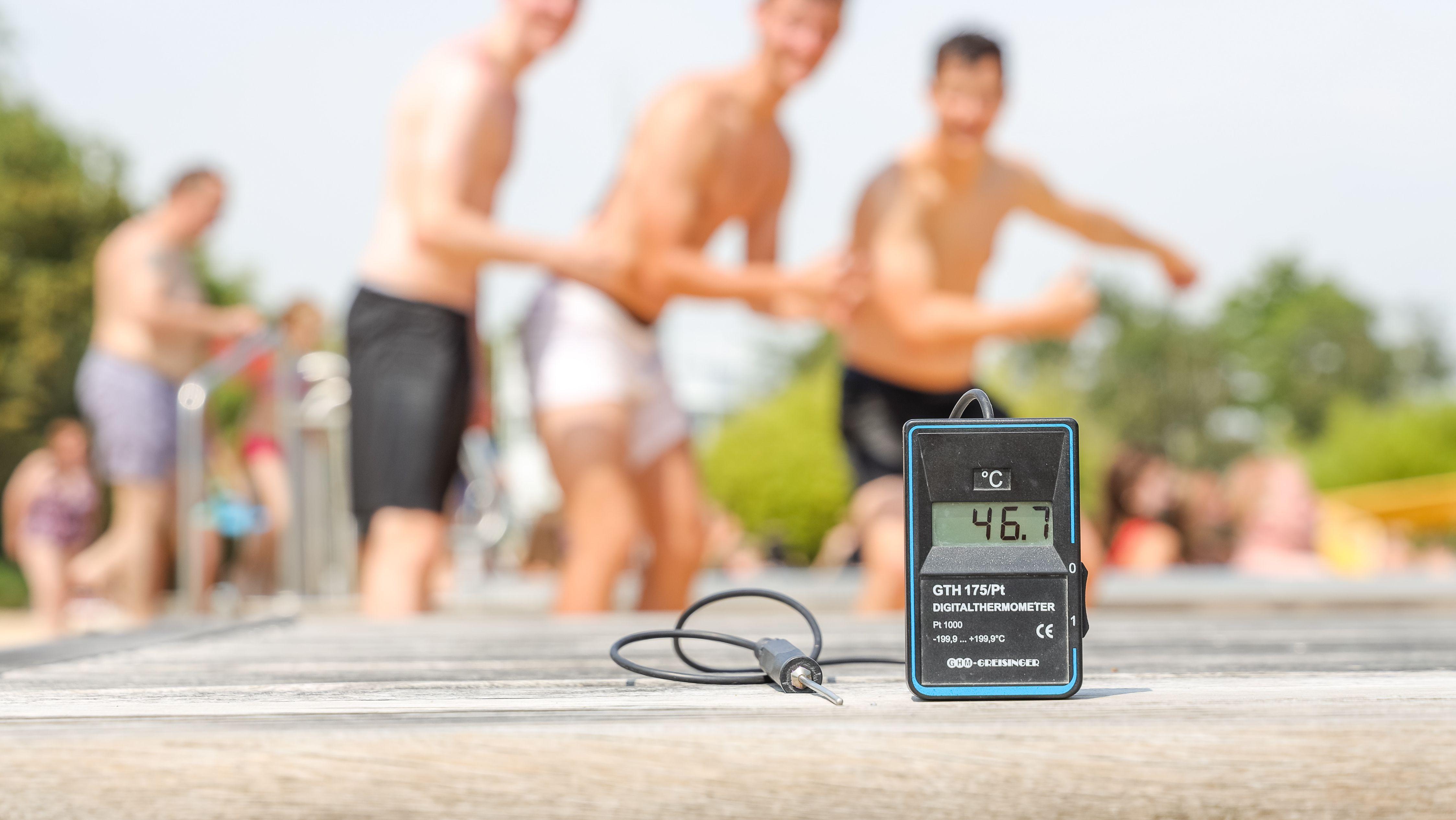 Die Anzeige eines Thermometers zeigt 46,9 Grad in der Sonne an, während im Hintergrund die Menschen im Schwimmbad sind. Eine neue Hitzewelle bringt Deutschland mit rekordverdächtigen Temperaturen zum Schwitzen.