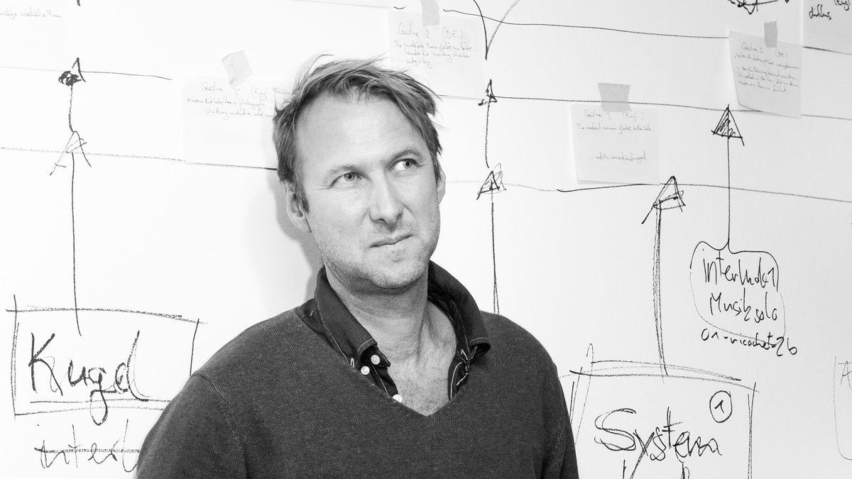 Ein Mann steht vor einer über und über mit Regieideen beschriebenen und mit Notizzetteln beklebten Wand