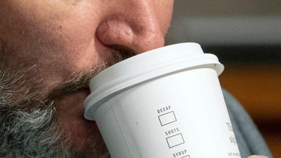 Ein Mann trinkt aus einem Papp-Kaffeebecher.