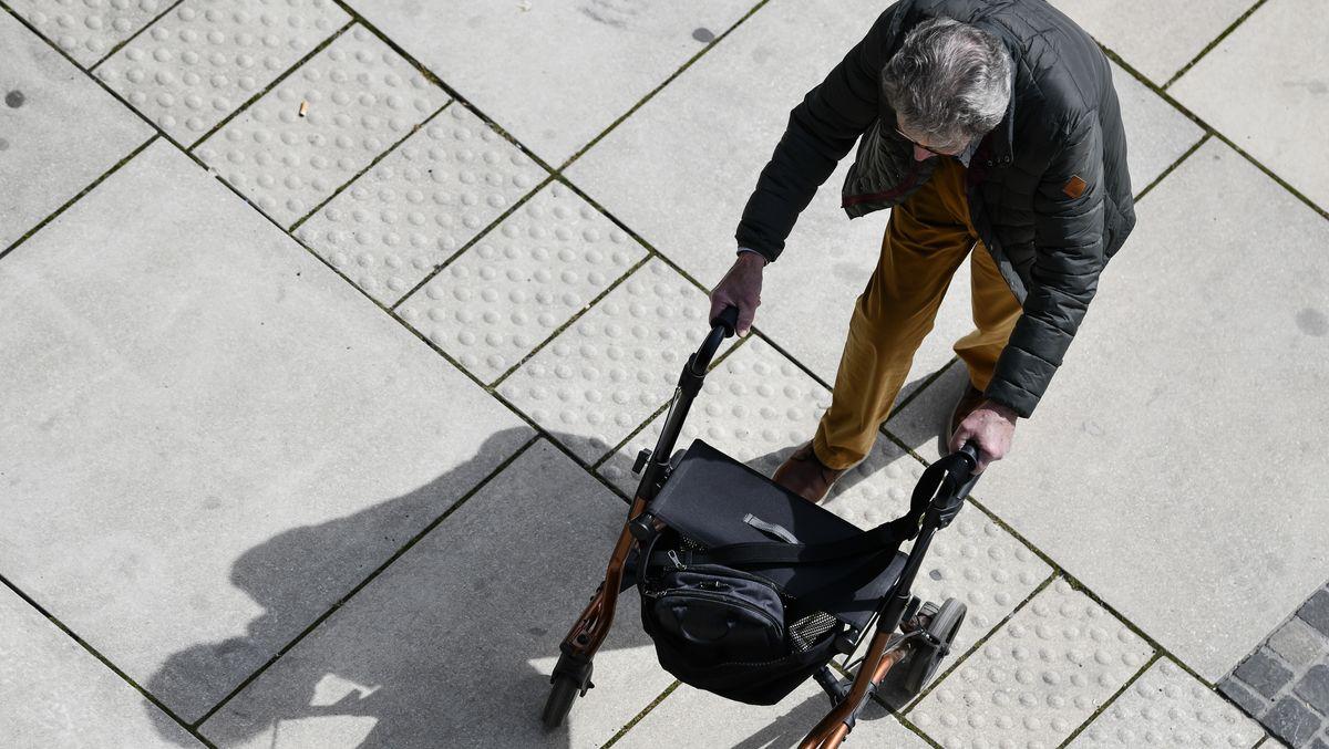 Ein alter Mann mit Rollator geht über einen Platz