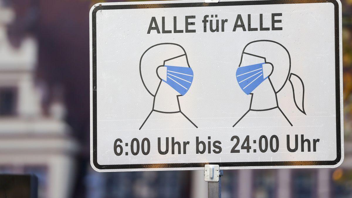 """Ein Schild """"Alle für Alle"""" und von """"6:00 Uhr bis 24:00 Uhr"""" weist am Eingang einer Innenstadt auf die Maskenpflicht hin."""