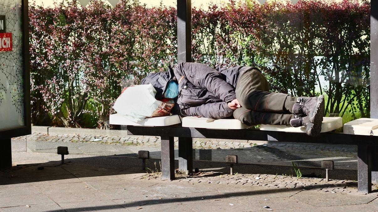 Ein Obdachloser liegt auf Sitzen