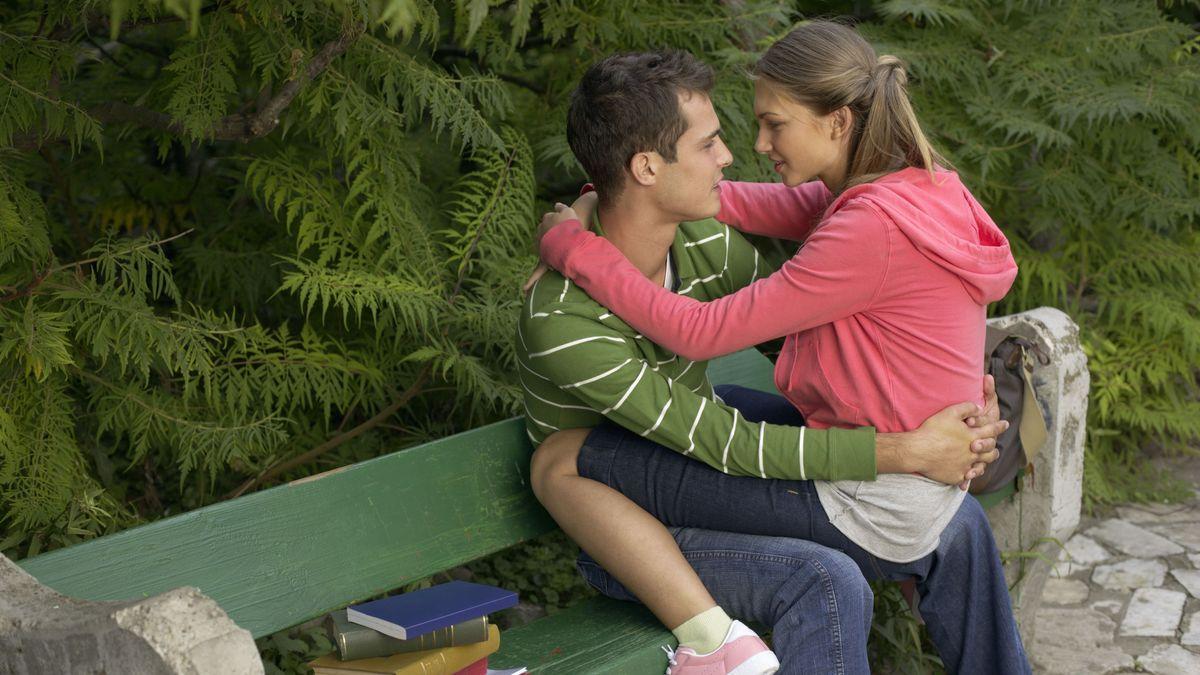 Zwei verliebte junge Menschen auf einer grünen Bank, die sich tief in die Augen schauen. Sie sitzt auf seinem Schoß