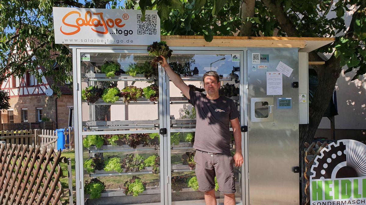 Gärtner Jochen Haubner steht vor dem Salat-Automaten und hält einen Salatkopf in die Höhe.