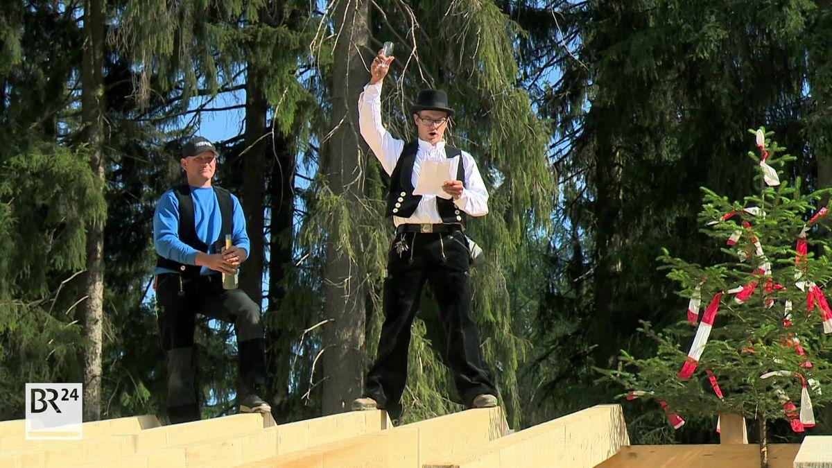 Zimmermannsleute stehen auf den Holzbalken, einer hebt ein Sektglas in die Höhe und spricht anlässlich des Richtfestes.