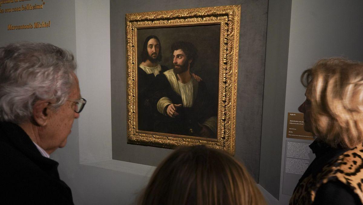 Drei Besucher kucken auf ein kleines Gemälde zweier Männer, das in einem dicken Goldrahmen an der Wand hängt.