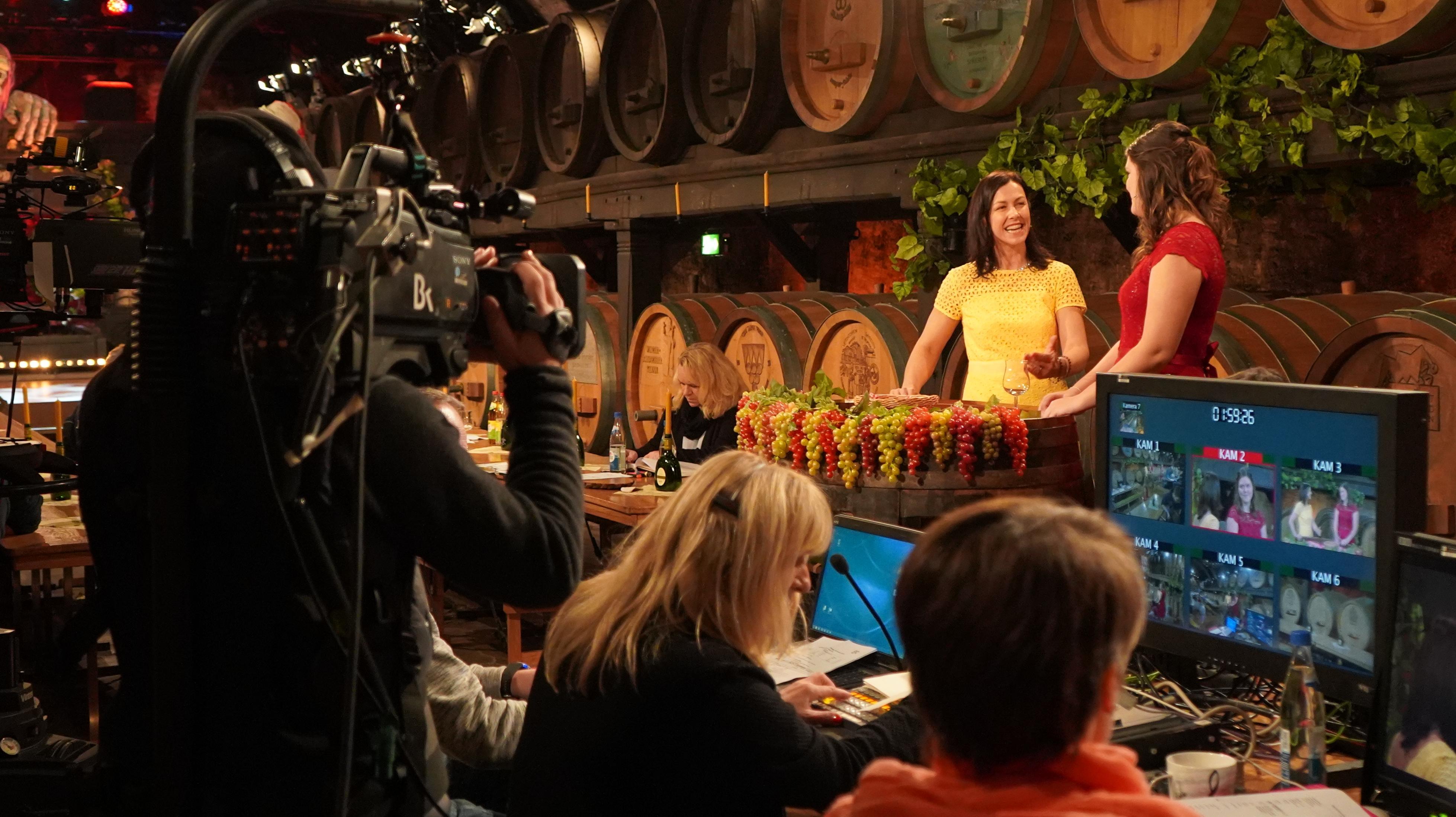 Ein Kameramann hält eine Kamera auf seiner Schulter - im Hintergrund Weinfässer und zwei Frauen, die sich unterhalten