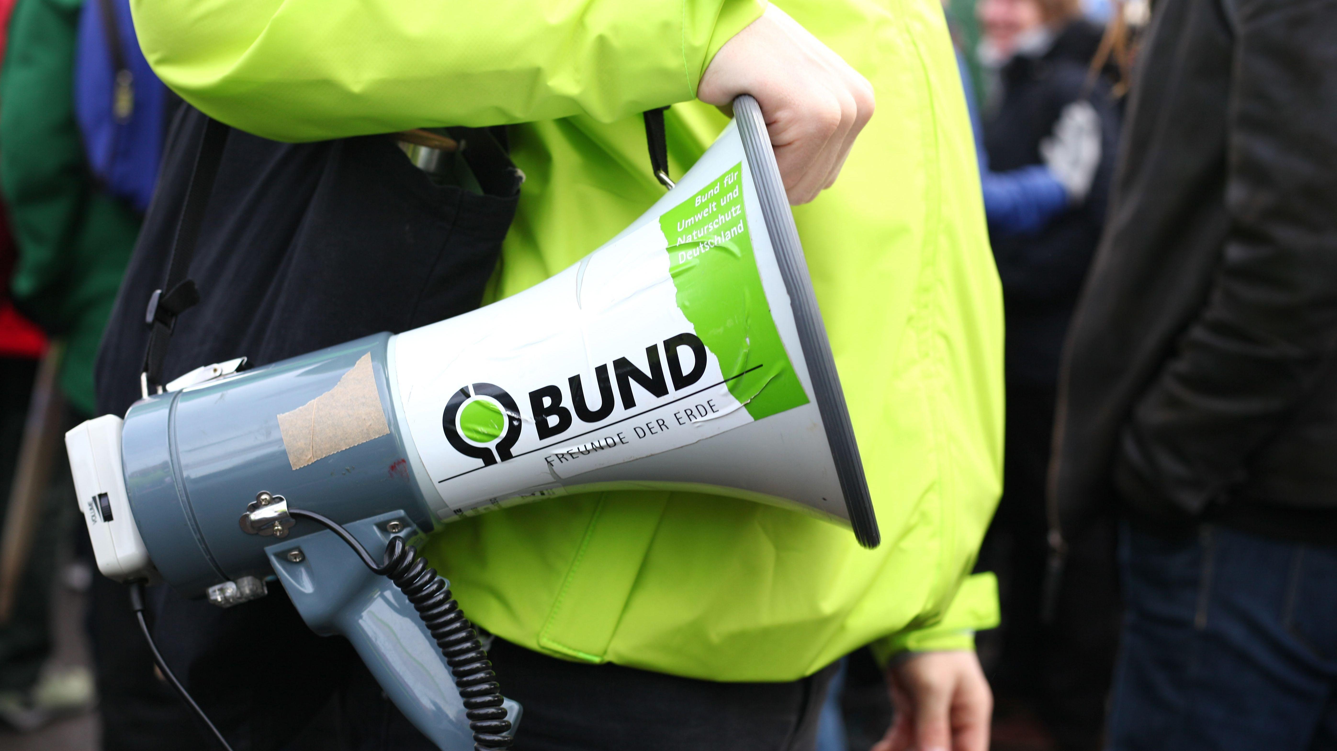 Bund Naturschutz kämpft gegen Flächenverbrauch und für Artenvielfalt: Demonstrant in neongrüner Jacke mit Megaphon in der Hand, auf dem ein Aufkleber des BUNDs geklebt ist