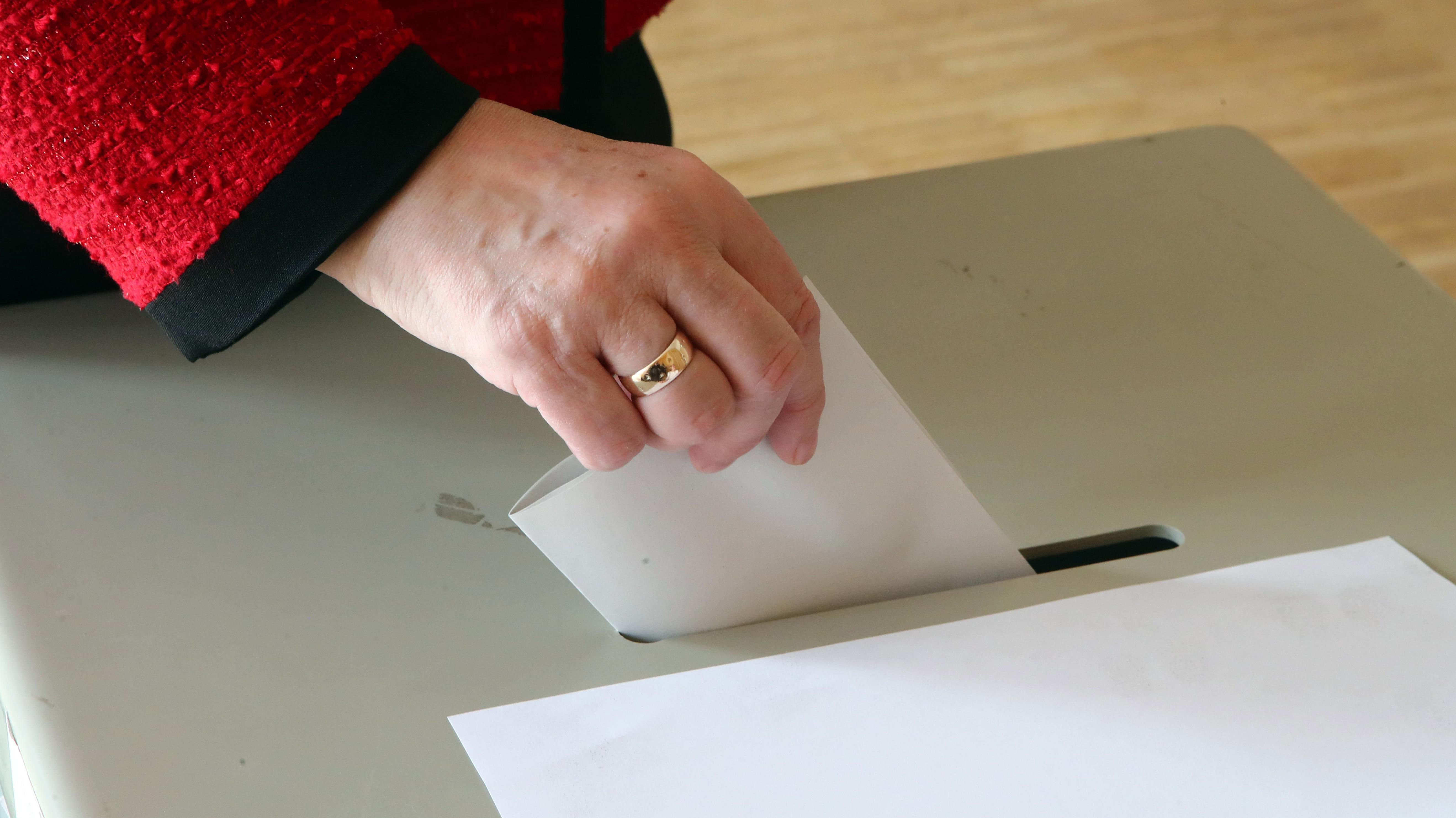 Eine Frau steckt den Wahlbrief in eine Wahlurne