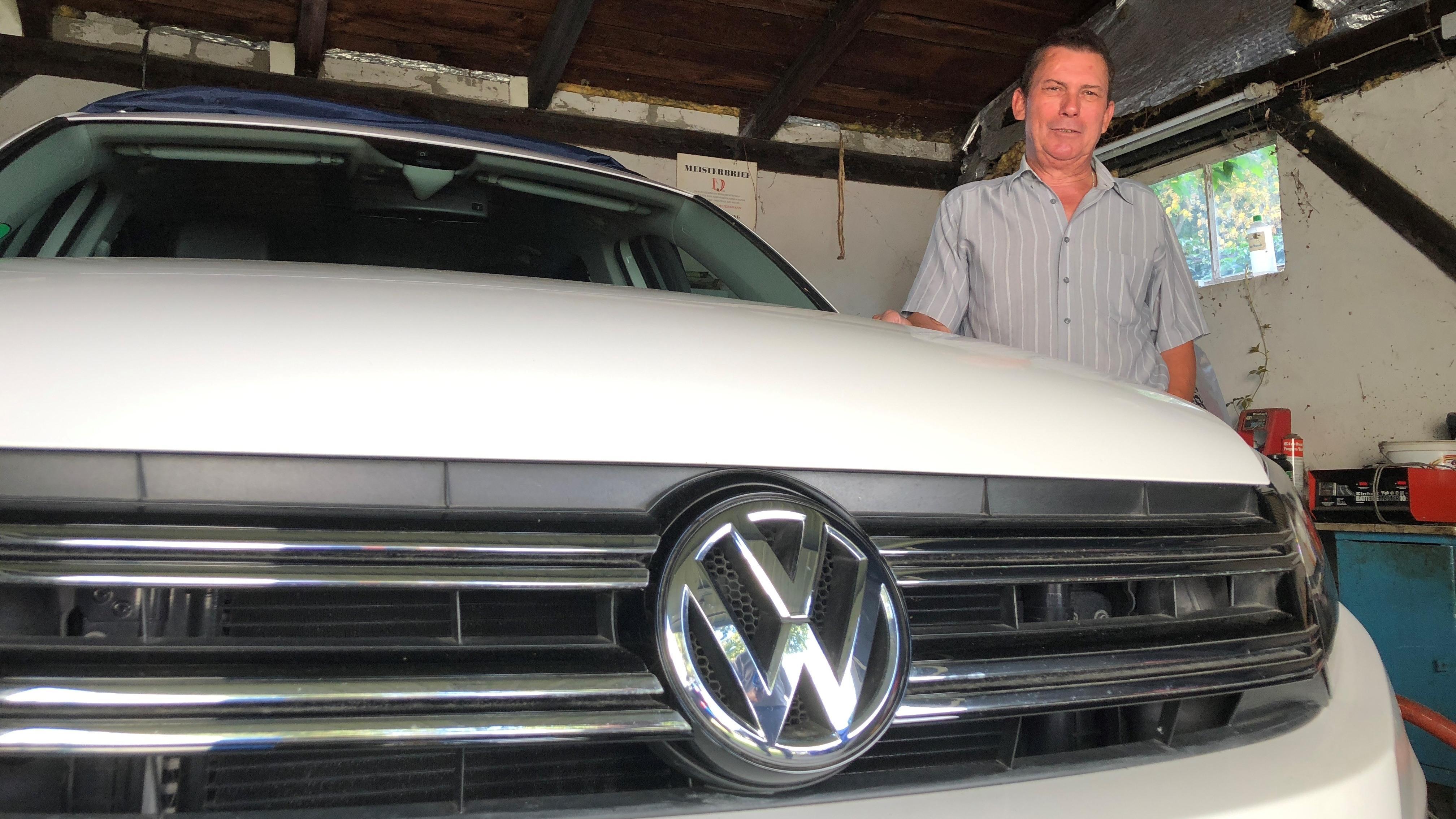 Christian Wiedenmann steht neben seinem VW Tiguan