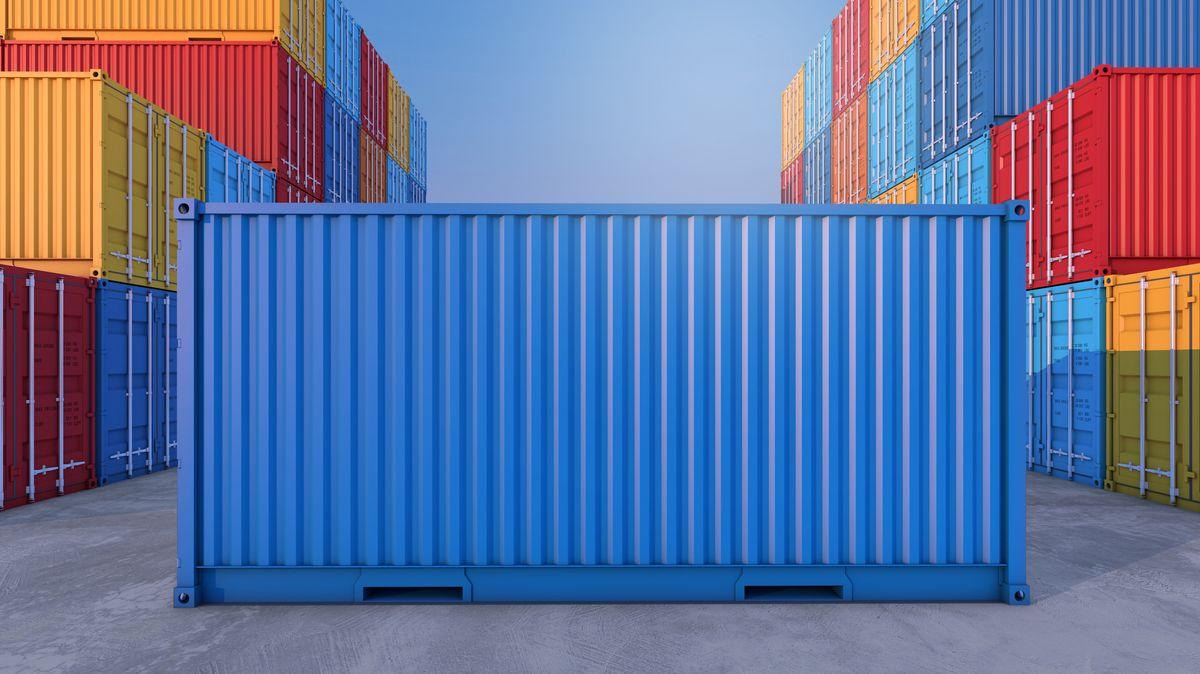 Ein blauer Container steht quer zwischen anderen Containern die orange, rot und blau sind.