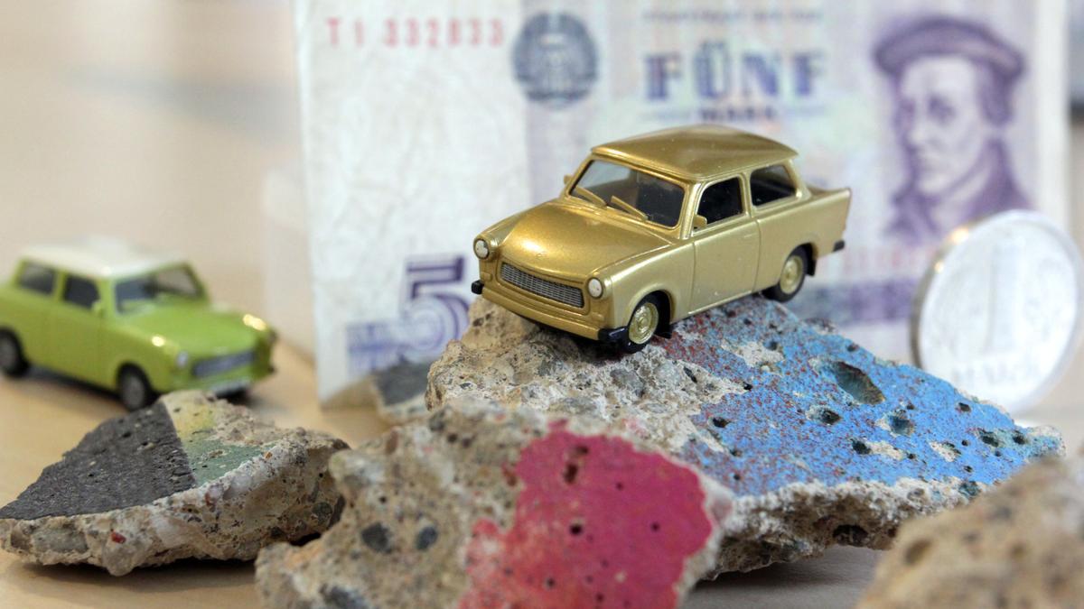Ein Spielzeug-Trabi steht auf Brocken der DDR-Mauer, im Hintergrund DDR-Mark-Schein und -Münze