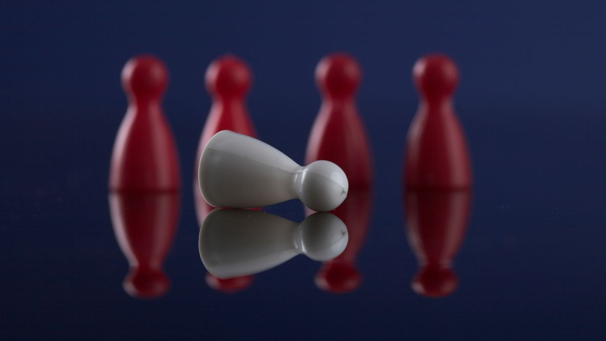 Symbolbild für Ausgrenzung: Vier rote Spielfiguren stehen im Hintergrund, eine weiße Spielfigur liegt im Vordergrund.