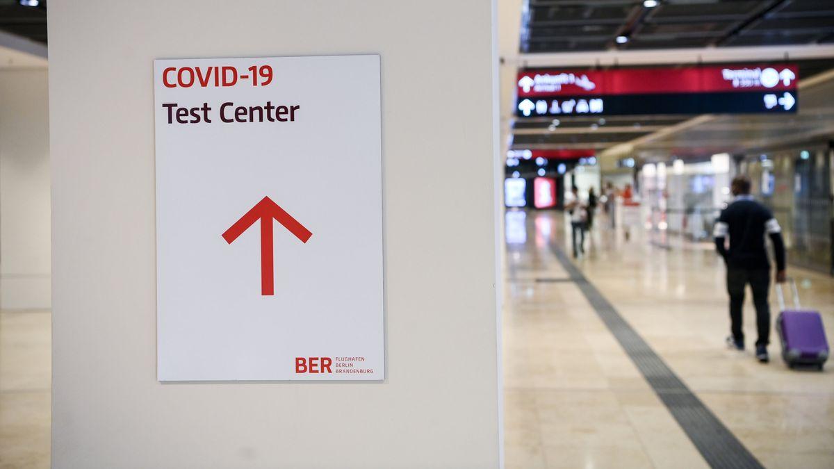 """Ein Reisender geht im Flughafen Berlin-Brandenburg (BER) mit einem Koffer nahe eines Hinweisschildes mit der Aufschrift """"Covid-19 Test Center""""."""