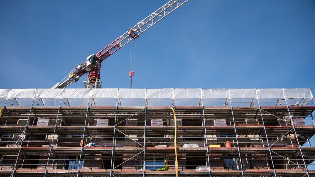 Ein Gerüst auf einer Baustelle an einem Neubau von einem Mehrfamilienhaus.