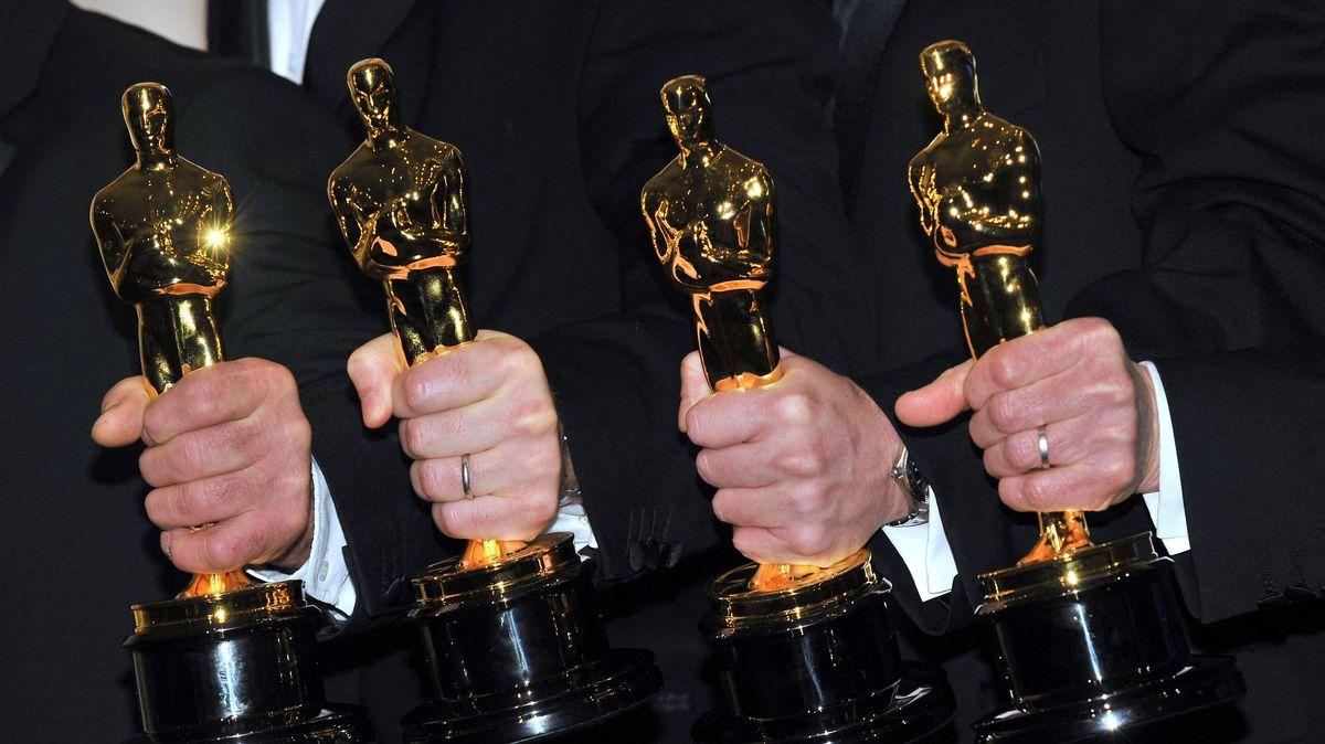 Vier Männer halten die goldene Trophäe in den Händen.