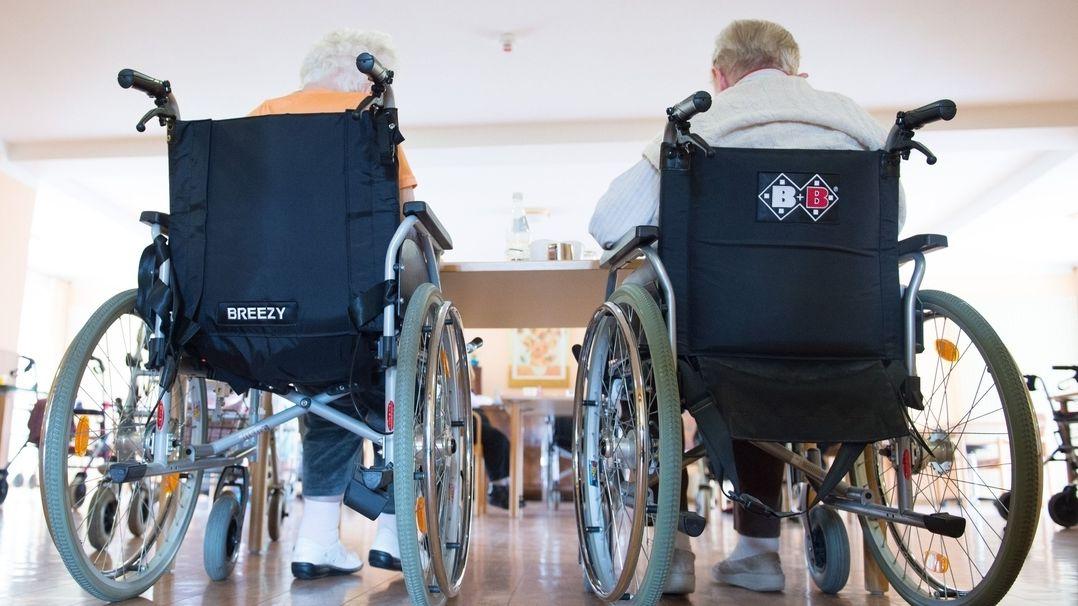Zwei pflegebedürftige Frauen sitzen in einem Pflegeheim in ihren Rollstühlen nebeneinander.