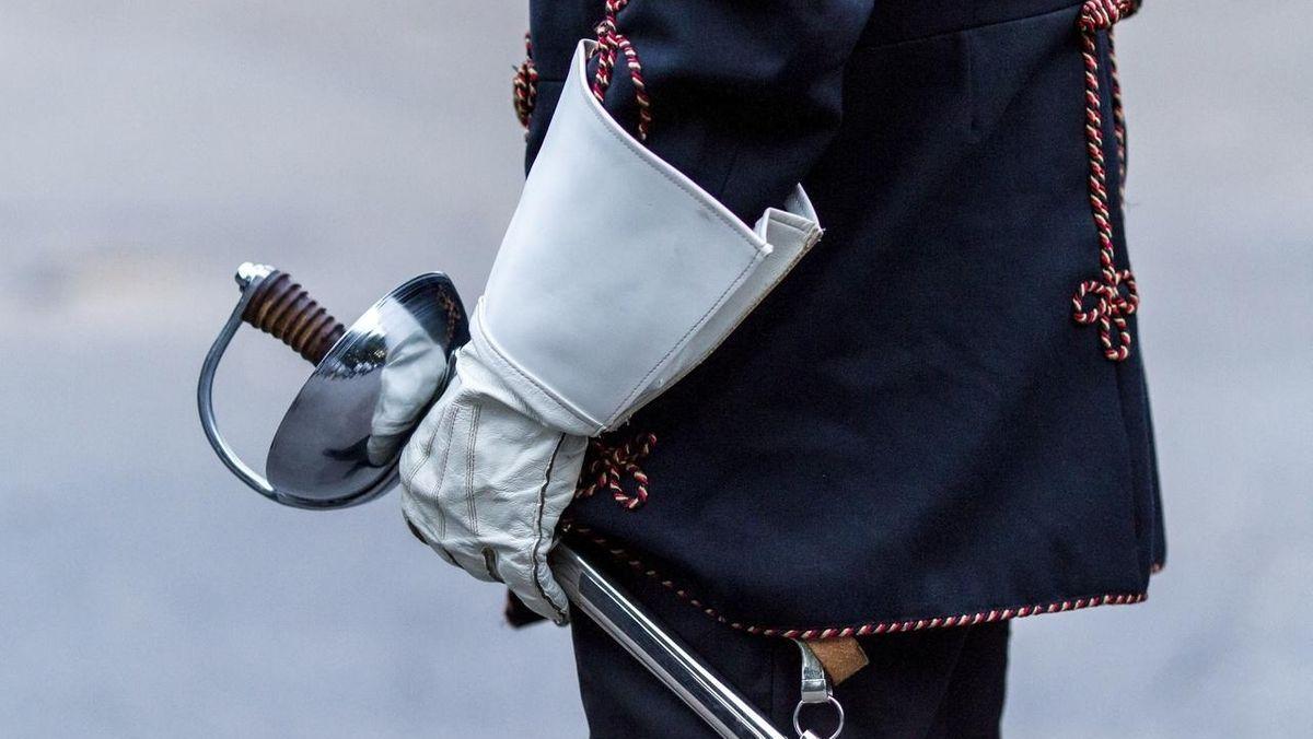 Symbolbild: Burschenschaften - eine Person ist mit einer Trachtenuniform gekleidet und hält einen Degen in der Hand.