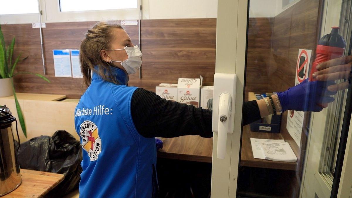 Mitarbeiter der Bahnhofsmission München geben durch eine Klappe Essen, Trinken, Kleidung und Hygieneartikel an Bedürftige aus.