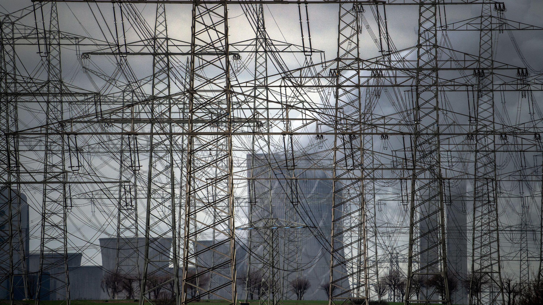 Nordrhein-Westfalen, Niederaußem: Strommasten stehen vor dem Braunkohlekraftwerk Niederaußem.