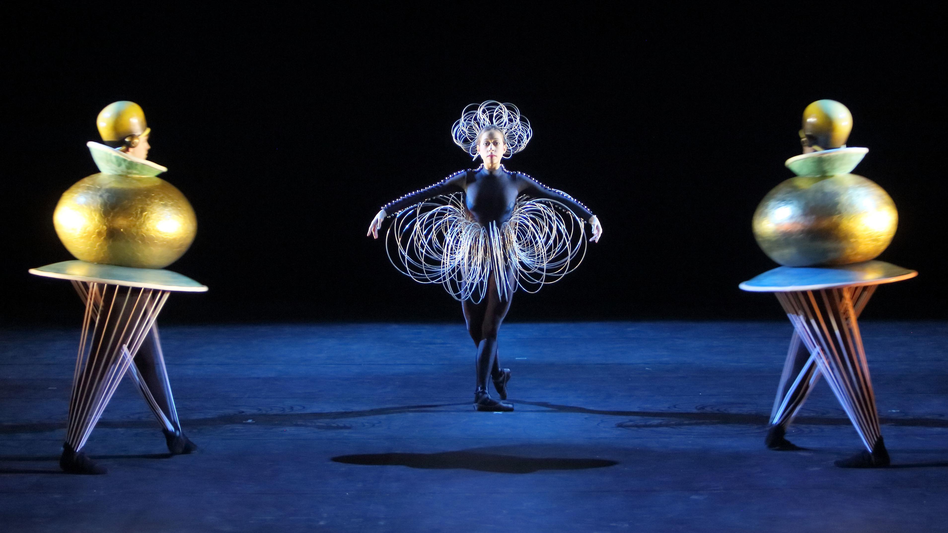 """""""Triadisches Ballett"""" nach Oskar Schlemmer: Drei Figuren mit Kegelbeinen und Kugelkörpern auf einer dunklen Bühne"""