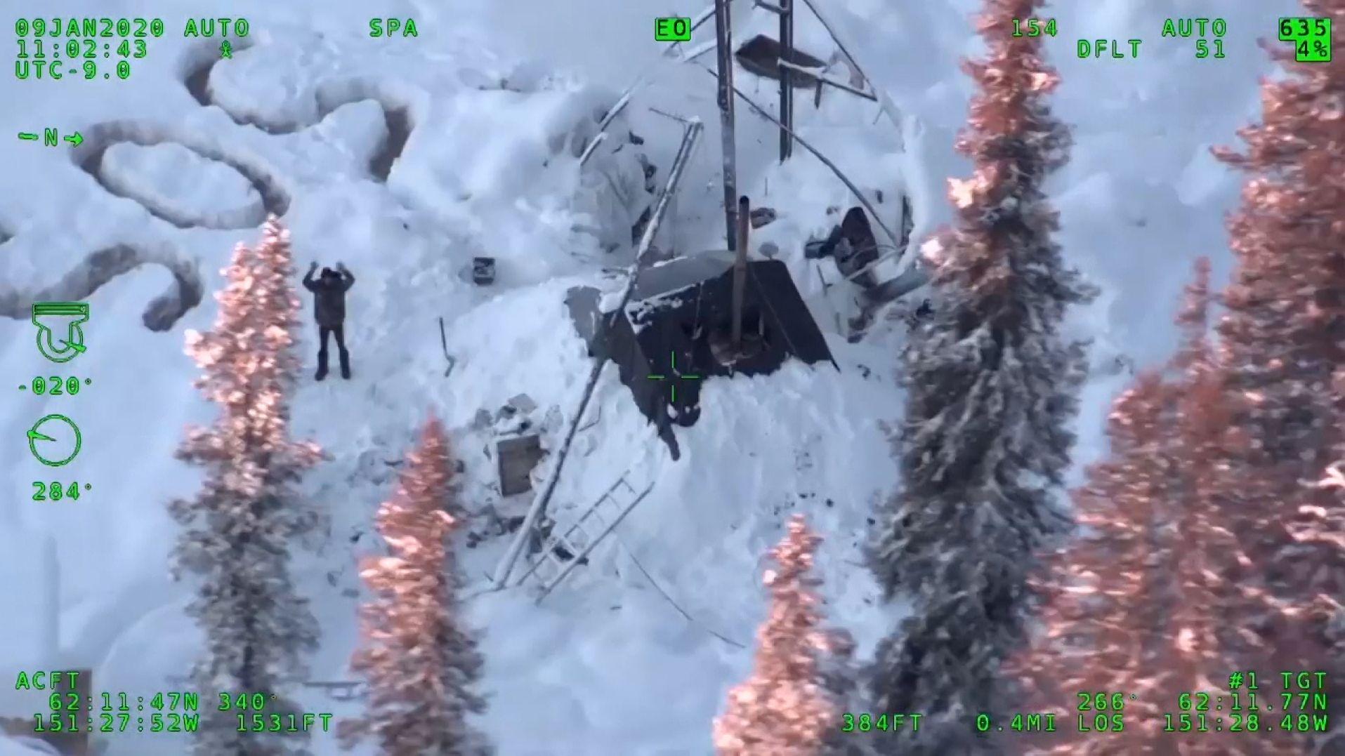 """Mann winkt neben eingestampften Buchstaben """"SOS"""" den Rettern im Helikopter zu"""