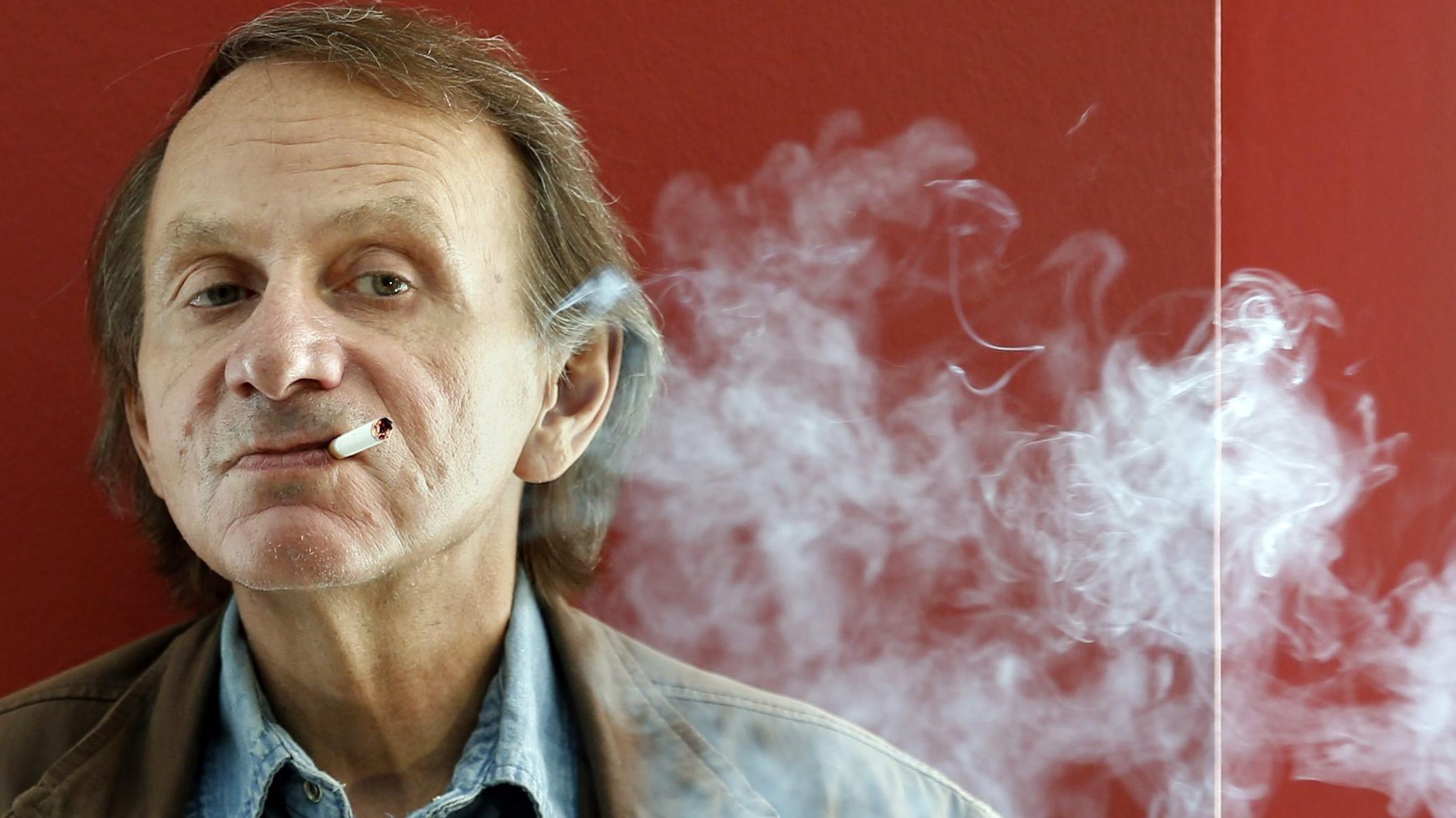 Porträt von Michel Houellebecq vor einer roten Wand, rauchend