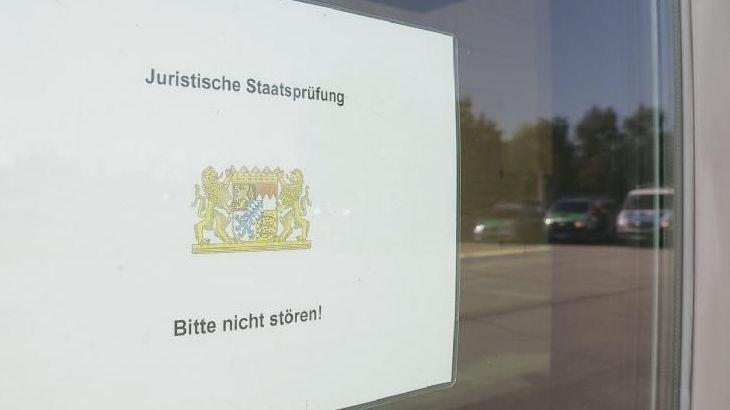 Schild am Eingang der Dreiländerhalle - in der der Tür spiegeln sich Polizei-Einsatzfahrzeuge