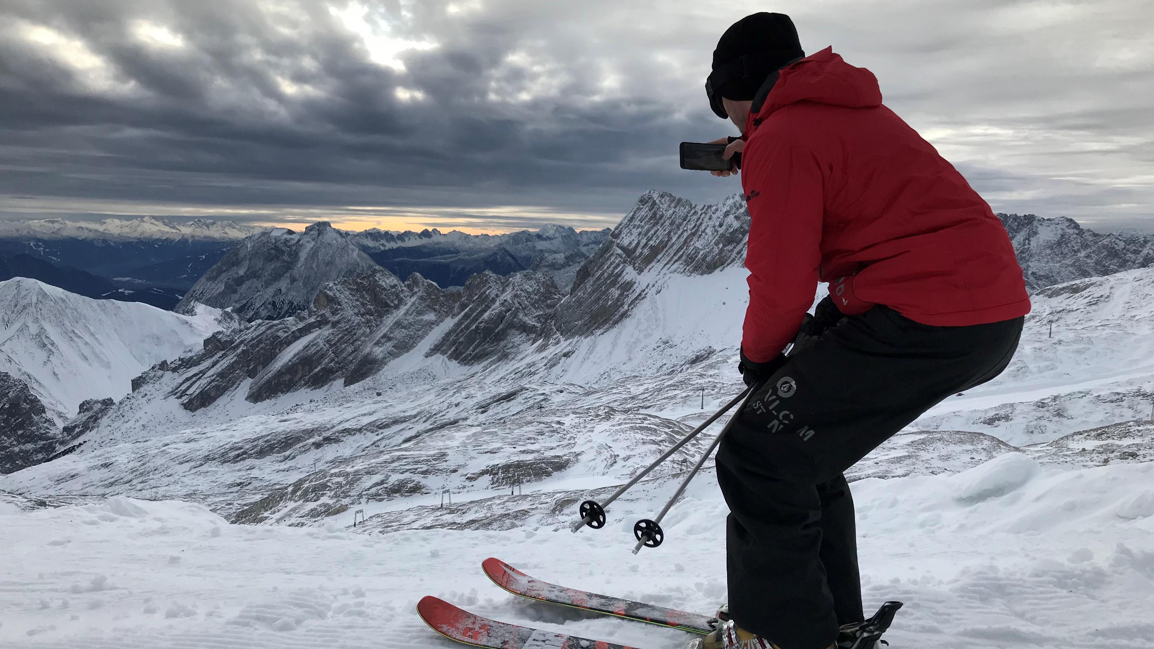 Ein Skifahrer auf der Zugspitze fotografiert die umliegenden Berge.