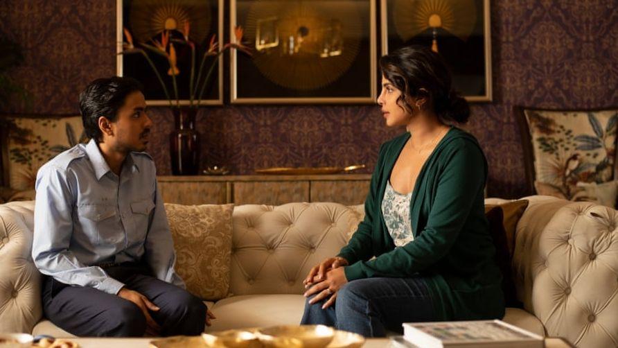 Junger Mann mit Schnauzbart und dunkelhaarige Frau sitzen auf einer Couch und sehen sich an.