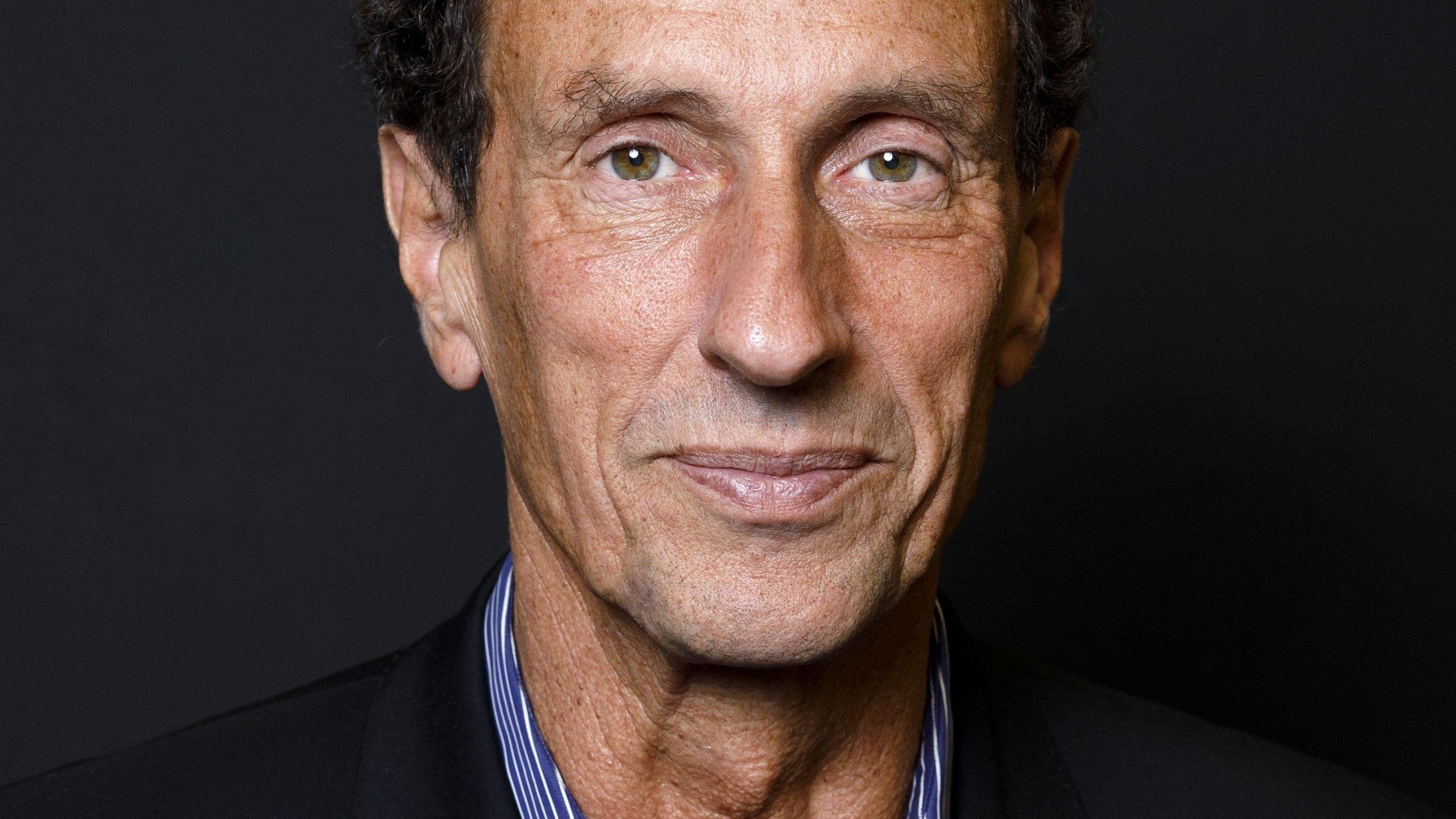 Philosoph Julian-Nida-Rümelin lächelt vor dunklem Hintergrund in die Kamera