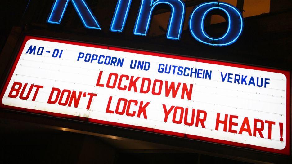 """Die Leuchtreklame eines Kinos zeigt den Schriftzug """"Lockdown - But don't lock your heart!"""""""