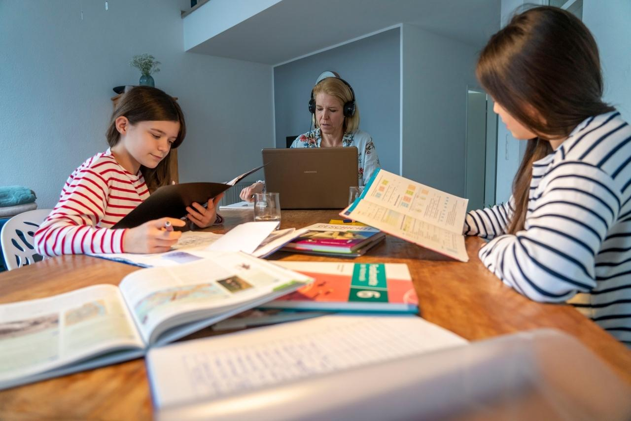 Homeschooling, während des Lockdowns. Kinder lernen zuhause für die Schule, ihre Mutter ist im Homeoffice.