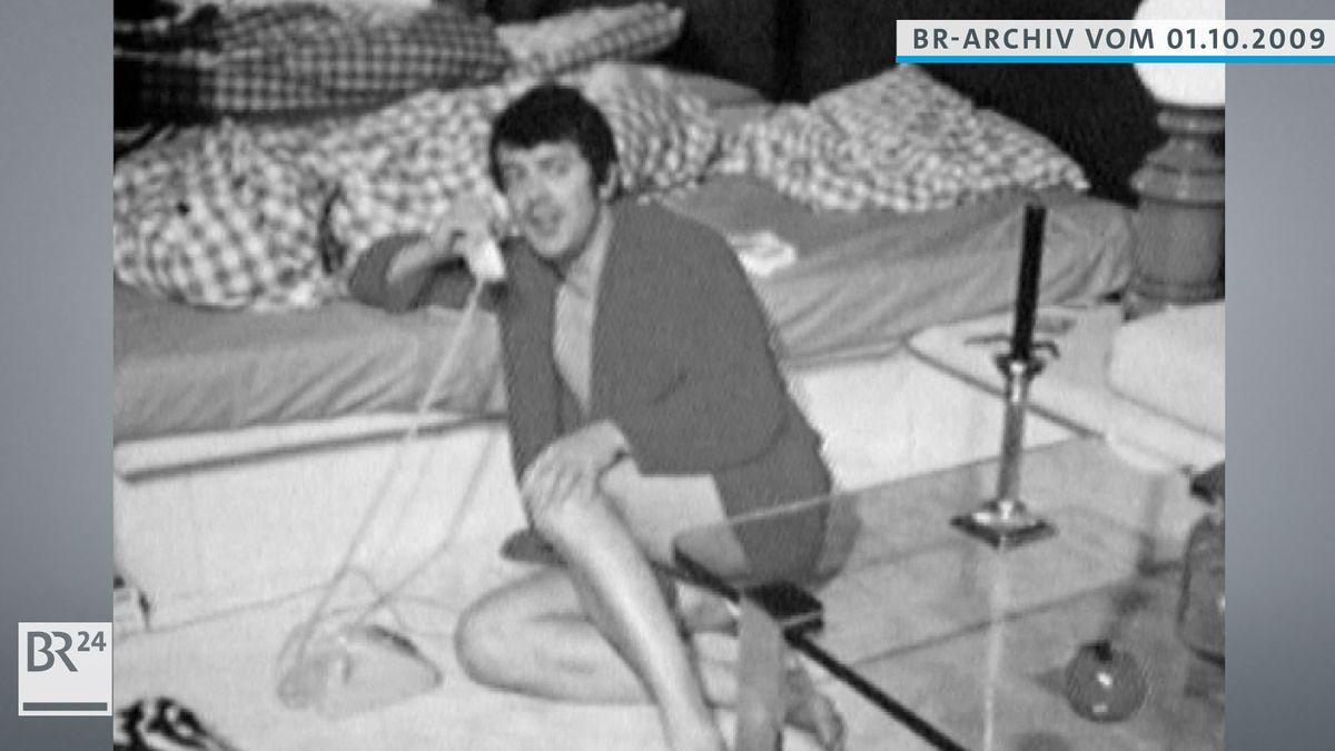 Michael Graeter, mit Bademantel auf dem Boden sitzend, telefoniert mit Festnetz-Wählscheibentelefon